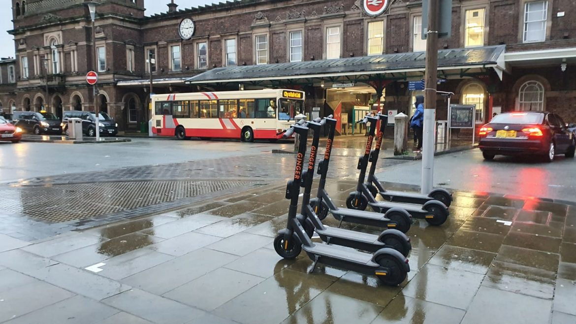 Ginger e-scooters parked outside Chester train station.
